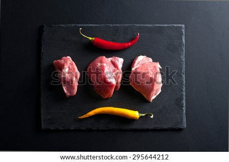 meat and chilli peppers on black slate background