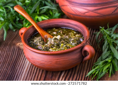 meat and greens soup in pottery with a wooden spoon on a brown wooden background with greens - stock photo