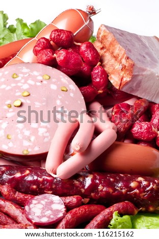 Meat and sausages on lettuce leaves. Isolated on white background from above. - stock photo
