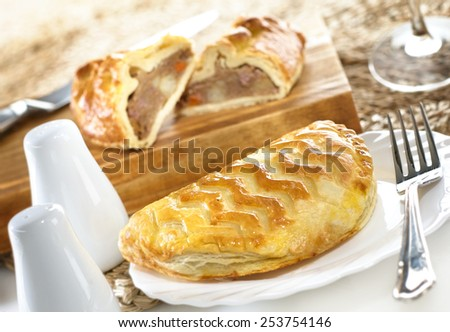 Meat and vegetable pasties in dining environment on plate and chopping board with knife and fork, salt and pepper and wine glass stem - stock photo