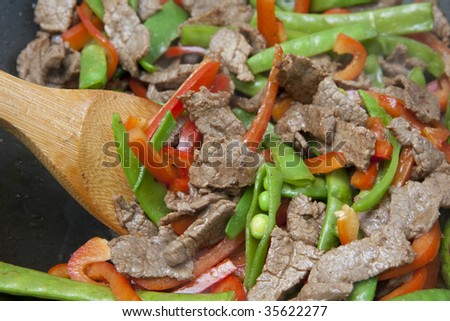 Meat and Vegetable stir-fry being cooked in wok - stock photo