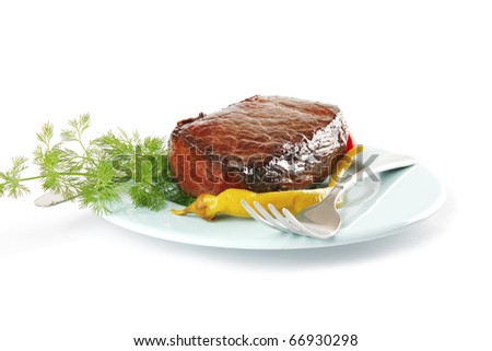 meat and vegetables on blue dish with pepper - stock photo