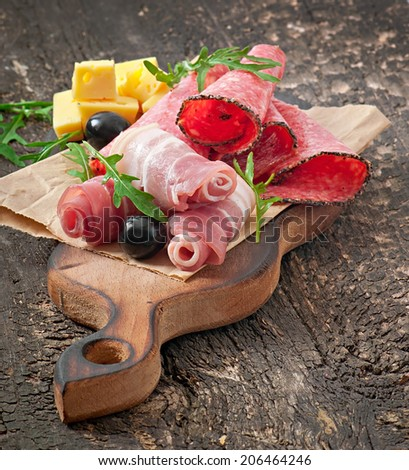 Meat appetizer on old wooden background - stock photo