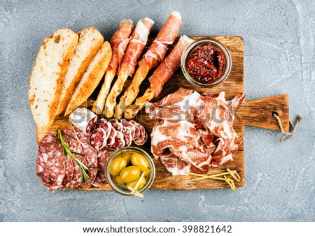 Meat appetizer selection or wine snack set. Variety of smoked meat, salami, prosciutto, bread sticks, baguette, olives and sun-dried tomatoes on rustic wooden board, top view, horizontal - stock photo