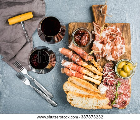 Meat appetizer selection. Prosciutto di Parma, salami, bread sticks, baguette slices, olives, sun-dried tomatoes on rustic wooden board, two glasses of red wine over grey concrete textured backdrop - stock photo