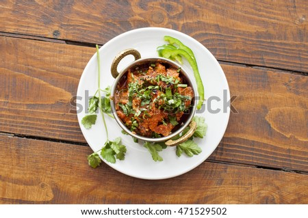 Meat curry food dish in a copper bowl on wood background