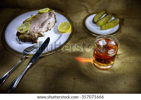 meat cutting on a table with cognac and vegetables