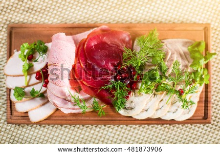meat delicatessen plate with pomegranate, dill and parsley.