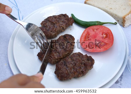 Meat dish at dinner table. Eating concept. Bread, grilled lamb meat, meatballs and liver dish, yogurt and water glass. Healthy protein diet concept. Hand to dip.