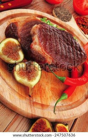 meat entree : grilled beef steak served with red hot cayenne peppers green stuff sweet figs and cutlery on wood plate over wooden table - stock photo
