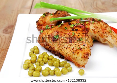 meat food : chicken legs garnished with green peas and hot chili peppers on white plates over wooden table - stock photo