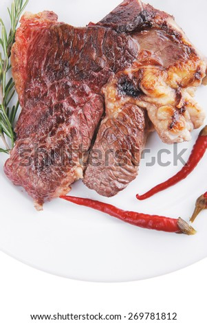 meat food : grilled beef steak on white plate with red thin pepper , spices and rosemary isolated over white background - stock photo