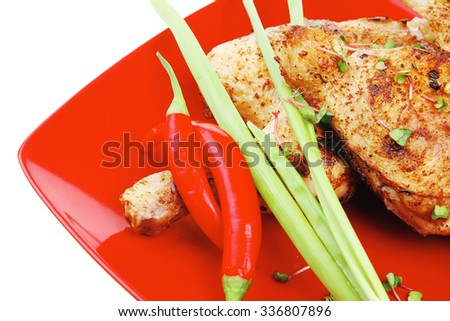 meat food : grilled quarter chicken garnished with green sprouts and red peppers on red plate isolated over white background - stock photo