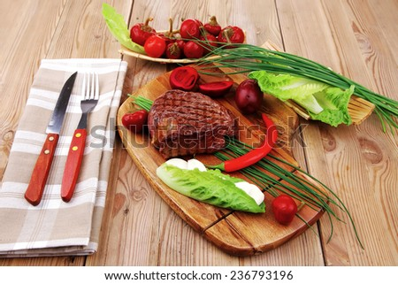 meat food : roast beef garnished with green staff and red chili hot pepper on wooden table with cutlery - stock photo