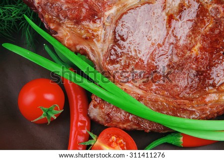 meat food : roast rib on dark dish with thyme pepper and tomato isolated over white background - stock photo