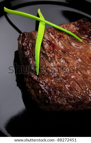 meat food : roasted fillet mignon on black plate with chili pepper and chives isolated over white background - stock photo