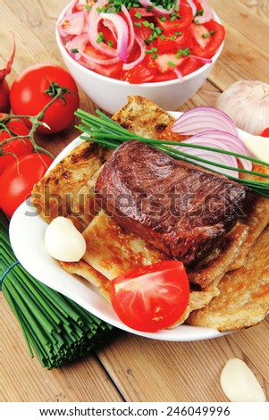 meat food : roasted fillet mignon on bread in white bowl garnished with tomatoes salad on wooden table - stock photo
