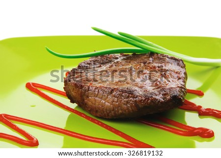 meat food : roasted fillet mignon on green plate with chives and ketchup isolated over white background - stock photo