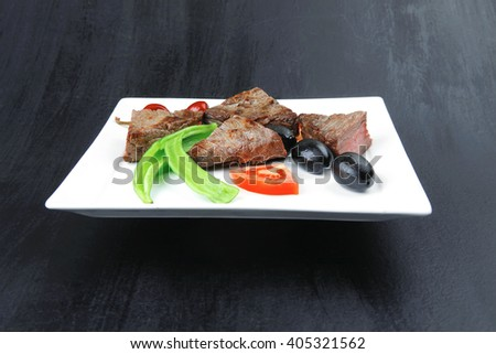 meat food : roasted fillet mignon on white plate with tomatoes apples and chili pepper over black wooden table - stock photo
