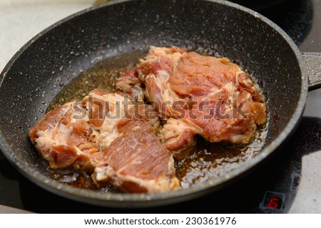 Meat frayed on fraying pan on modern stove - stock photo