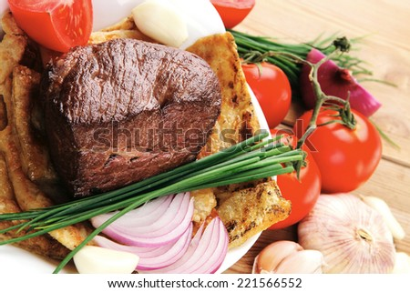 meat : grilled beef fillet mignon on bread with tomatoes salad on wooden table - stock photo