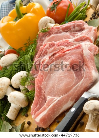 Meat, herbs and vegetables on the cutting board. Shallow dof.