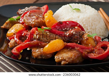 Meat in a spicy sauce, sweet pepper and tangerines with a garnish of boiled rice - stock photo