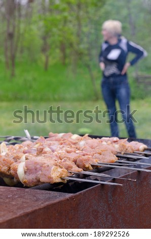 Meat kebabs cooking over a summer BBQ at a rural campsite with a woman standing in the background with focus to the meat - stock photo