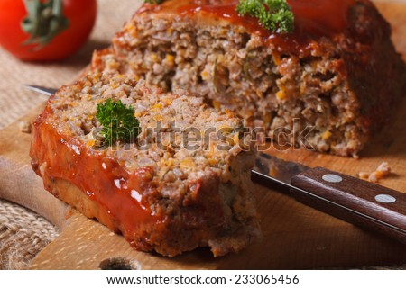 meat loaf with ketchup and vegetables close-up on chopping board. horizontal  - stock photo