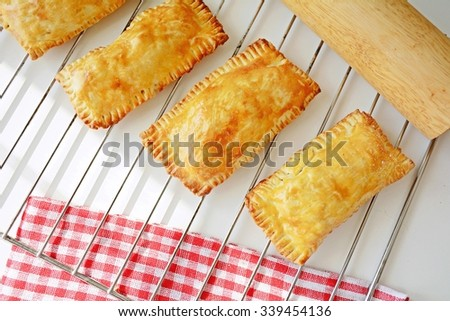 Meat pastries on cooling rack, high angle view - stock photo