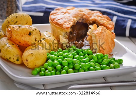 Meat pie with new potatoes and peas. - stock photo