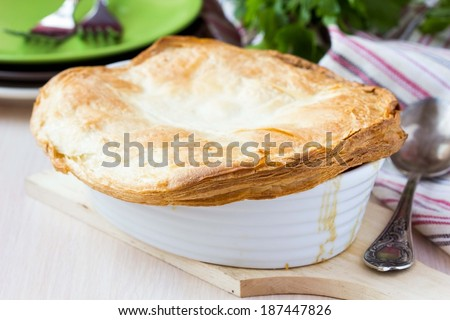 Meat pie with stew of chicken, mushrooms, peas, puff pastry crust, tasty homemade dish - stock photo