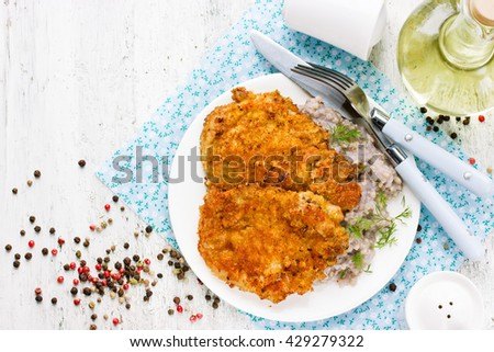 Meat pork chop in bread crumbs garnished with green buckwheat, hearty and healthy lunch dish top view blank space for text - stock photo