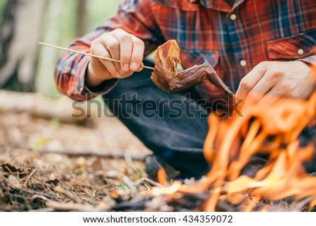 Meat rabbit cooked on fire. Camping. fire outdoors. delicious summer picnic. bushcraft concept - stock photo