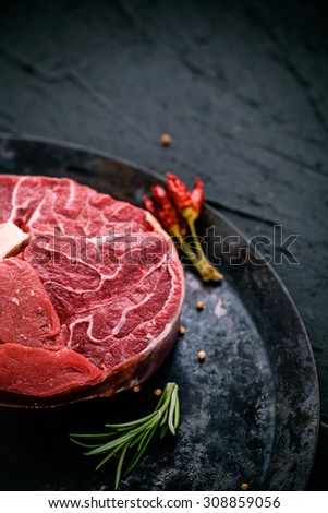 Meat. Raw meat steak on black with herbs - stock photo
