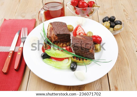 meat savory : beef fillet mignon grilled and garnished with baked apples , tomatoes and juice on wooden table - stock photo