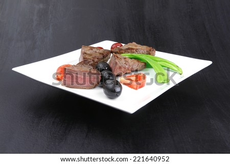 meat savory : grilled beef fillet mignon on white plate with tomatoes apples and pepper over black wooden table - stock photo
