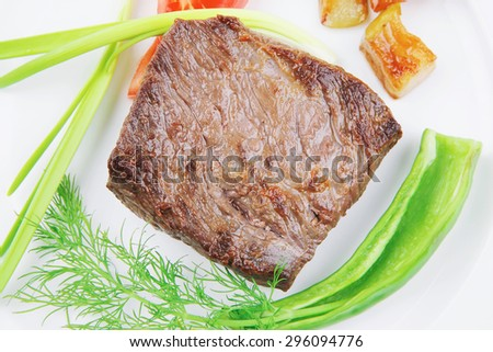 meat savory : grilled beef fillet mignon on white plate with tomatoes apples and pepper over wooden table - stock photo