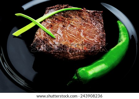 meat savory : grilled beef fillet mignon served on black plate isolated over white background with chili pepper - stock photo