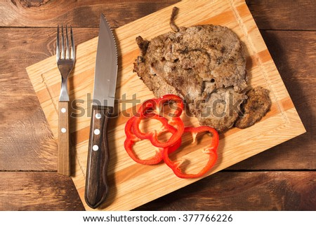 Meat steak whit fresh red bell pepper, knife and fork,on a wooden background - stock photo