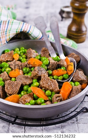 Meat stew with peas and carrots in a rustic style. Selective focus.