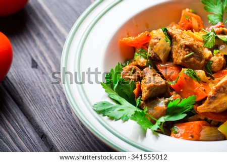 Meat stew with vegetables and herbs on dark wooden background - stock photo