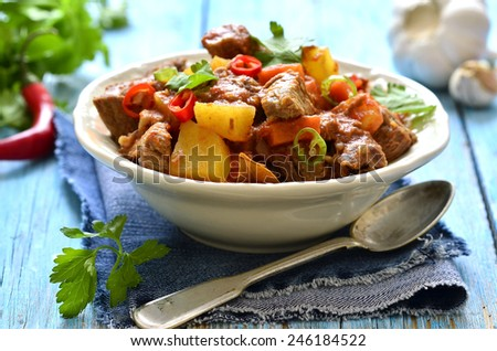 Meat stewed with vegetable in spicy tomato sauce on a wooden table. - stock photo