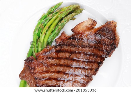 meat table : rare medium roast beef fillet and asparagus served on white dish