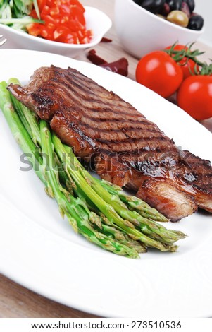 meat table : rare medium roast beef fillet and pasta with tomatoes asparagus and several kinds of olives, served on white dish over light wood - stock photo
