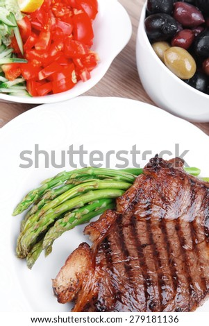meat table : rare medium roast beef fillet and pasta with tomatoes asparagus and several kinds of olives, served on white dish over light wood