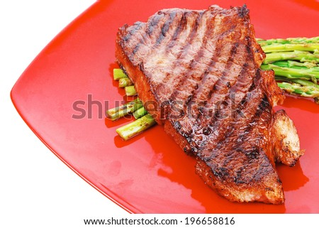 meat table : rare medium roast beef fillet asparagus served on red dish isolated over white
