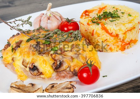 Meat under cheese and mushrooms with rice - stock photo