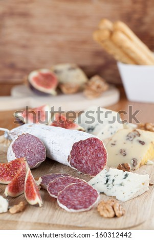 Meat with cheese, figs, nuts and grissini - stock photo