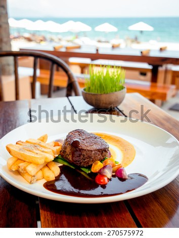 Meat with fried potatoes and salad dressed with sauce on a white plate. The Restaurant - stock photo